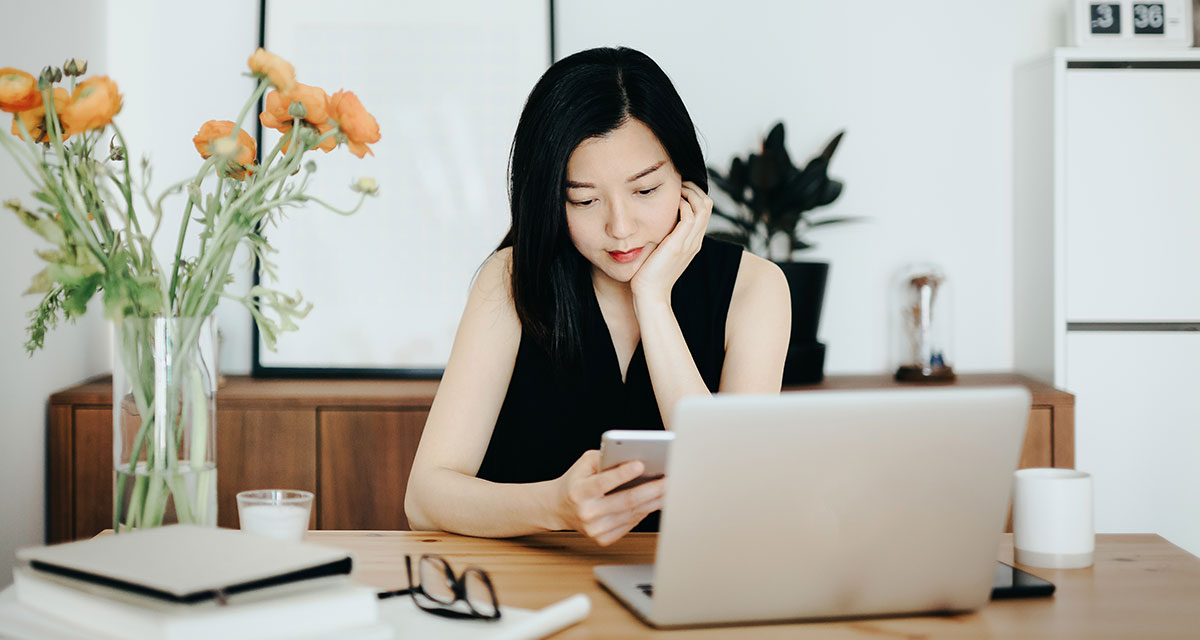 Woman working from home on her laptop and mobile phone